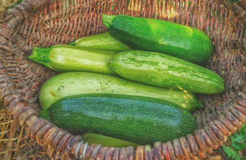 green cucumbers on round brown wicker basket
